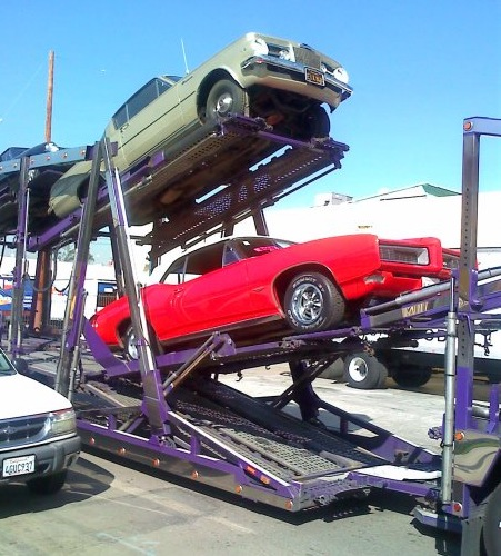 Dennis Buys Classic Cars car hauler with red Pontiac GTO and Plymouth Barracuda